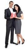 Det romantiska paret med gåvaasken, den iklädda svarta dräkten för folk, man ger gåvan till kvinnan som isoleras på vit bakgrund Arkivbilder