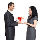 Det romantiska paret med gåvaasken, den iklädda svarta dräkten för folk, man ger gåvan till kvinnan som isoleras på vit bakgrund Royaltyfria Foton