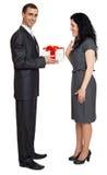 Det romantiska paret med gåvaasken, den iklädda svarta dräkten för folk, man ger gåvan till kvinnan som isoleras på vit bakgrund Royaltyfri Foto