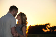 Det romantiska sinnliga barnet kopplar ihop förälskat posera på solnedgången Arkivbilder