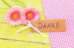 Det rosa färgblommor och kortet med det tyska ordet, Danke, hjälpmedel tackar dig Royaltyfri Bild