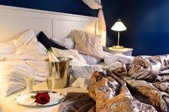 Det rumpled romantiska sovrummet täcker hotellchampagne ösregnar Arkivfoton