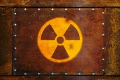 Det runda gula radioaktiva symbolet för varning för fara för joniseringsutstrålning som målades på en massiv rostig metallplatta, Arkivbild
