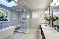 Det rymliga badrummet i grå färger tonar med upphettade golv royaltyfri bild