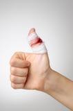 Det sårade fingret med blodigt förbinder Arkivfoto