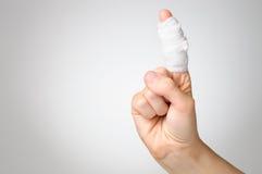 Det sårade fingret med förbinder Arkivbild