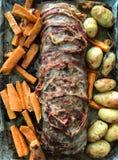 Det söndag hemmet gjorde lunch: danandet av en ugn bakade köttfärslimpan som täcktes i bacon, med potatisar och sötpotatisen på s royaltyfria bilder