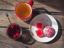 Det söta mellanmålet med tranbärmarshmallowen och marmelad, te i ett stort keramiskt rånar och en exponeringsglaskrus med körsbär royaltyfri bild
