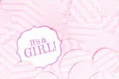 Det ` s ett flickatecken på baby showerpartiet Rosa färgen mönstrar bakgrund Baby showerberömbegrepp Royaltyfria Foton