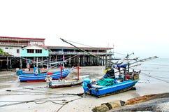 Det sandstranden och havet med fiskebåten, som parkerade på det beachfront med, vaggar arkivbild