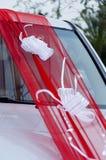 Det scharlakansröda bandet med vit organza bugar på en vit bröllopbil Arkivfoto