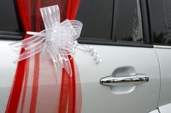 Det scharlakansröda bandet med vit organza bugar på en vit bröllopbil Arkivbilder