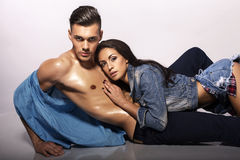 Det sexiga passionerade paret i jeans beklär att posera i studio Royaltyfria Bilder