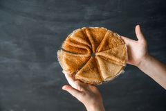 Det Shrovetide begreppet En bunt av vikta pannkakor på en platta i kvinnlighänder på en svart svart tavla mot en bakgrund Royaltyfri Foto