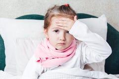 Det sjuka barnet som ligger i sängen och, trycker på henne forehaed arkivbilder