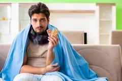 Det sjuka lidandet för ung man från influensa hemma arkivbild