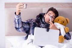 Det sjuka manlidandet från influensa i sängen royaltyfri bild