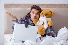 Det sjuka manlidandet från influensa i sängen royaltyfria bilder