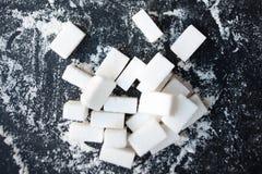 Det sjukliga matbegreppet - sockra och pudra på en svart bakgrund royaltyfri bild