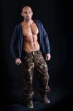 Det skalliga anseendet för ung man med den öppen tröjan och militär flåsar Arkivbild