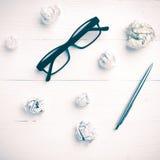 Det skrynkliga papper och glasögon med penntappning utformar Arkivbilder