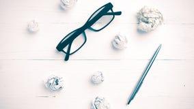 Det skrynkliga papper och glasögon med penntappning utformar Arkivbild