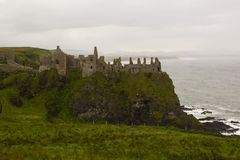 Det skuggigt fördärvar av den medeltida irländareDunluce slotten på klippaöverkanten som förbiser Atlanticet Ocean i Irland Arkivfoto