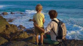 Det Slowmotion skottet av en fader och sonen som sitter på, vaggar att se närliggande vågor för ett hav den Tanah lotttemplet arkivfilmer