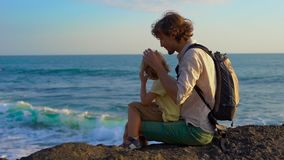 Det Slowmotion skottet av en fader och sonen som sitter på, vaggar att se närliggande vågor för ett hav den Tanah lotttemplet stock video