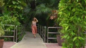 Det Slowmotion skottet av en härlig ung kvinna i ett tropiskt parkerar att gå och att vinka hennes långa hår stock video