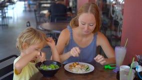 Det Slowmotion skottet av en ung kvinna och hennes son äter kinesisk mat i ett gatakafé lager videofilmer