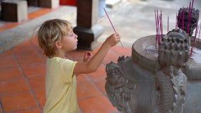 Det Slowmotion skottet av pojken i en buddistisk tempel sätter lite en aromatisk pinne i en rökelsekar arkivfilmer