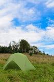 Det sluttande tältet i äng med stort vaggar i bakgrund Royaltyfria Bilder
