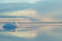 Det smältande isberget på vårbergsjön i inställningssolen Royaltyfri Fotografi