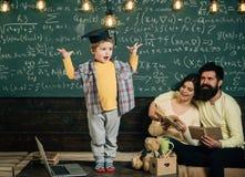 Det smarta barnet i doktorand- lock gillar att utföra Pojke som framlägger hans kunskap till mamman och farsan Föräldrar som lyss Royaltyfri Foto