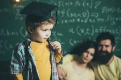 Det smarta barnet i doktorand- lock gillar att utföra Pojke som framlägger hans kunskap till mamman och farsan Föräldrar som lyss Arkivfoton