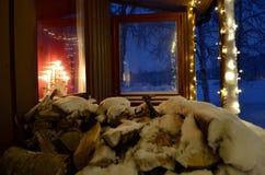 Det snö täckte burchträdvedträt loggar in det jul dekorerade huset Arkivfoton