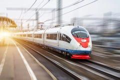 Det snabba drevet rider på den hög hastigheten på järnvägsstationen i staden fotografering för bildbyråer