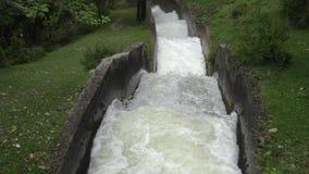Det snabba flödet av vatten i den konkreta kanalen stock video
