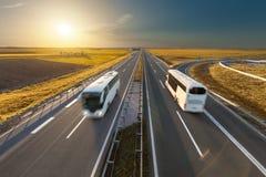 Det snabba loppet bussar på huvudvägen på den idylliska solnedgången Royaltyfria Bilder