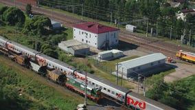 Det snabba passageraredrevet rider vid järnvägen förbi byn, antennskott Ryssland september 2018 arkivfilmer
