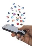 Det sociala massmedia som symboler flyger av iphonen räcker in Royaltyfri Foto