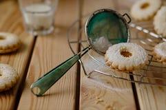 Det sockrade Linz kexet med persikamarmelad med ett exponeringsglas av mjölkar I Royaltyfri Foto