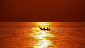 Det sol- fartyget körde över yttersidan av havet på soluppgång kontur av det lilla fartyget Royaltyfri Fotografi