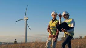 Det solbelysta fältet med en väderkvarn får korsat av två talande specialister Rent eco-vänskapsmatch energibegrepp lager videofilmer