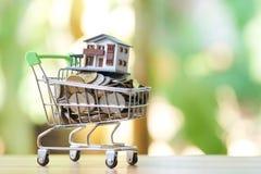 Det sparande pengarbegreppet av att samla myntar thailändska pengar i en modell för shoppingvagn och huspå naturbakgrund som bakg arkivfoto