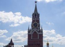 Det Spasskaya klockatornet av MoskvaKreml och vit fördunklar i blå himmel i solig dag Royaltyfri Foto