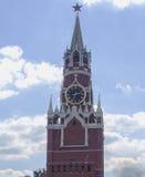 Det Spasskaya klockatornet av MoskvaKreml och vit fördunklar i blå himmel i solig dag Arkivbild