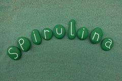 Det Spirulina ordet med målad gräsplan stenar sammansättning över grön sand Arkivfoto
