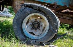 Det sprängda gummihjulet av ett jordbruks- maskineri royaltyfria foton